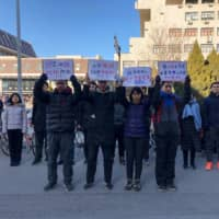 Students hold up signs as they protest against the change in a student-run Marxist group's leadership at Peking University in Beijing on Friday. | AFP-JIJI