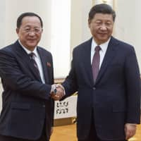Chinese President Xi Jinping shakes hands with North Korean Foreign Minister Ri Yong Ho at the Great Hall of the People in Beijing on Friday. | POOL / VIA AP