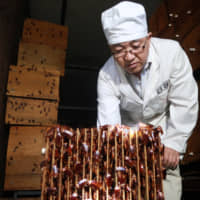 A staff member shows off cockroaches in shelves at a farm operated by pharmaceutical company Gooddoctor in Xichang, China, in August. | REUTERS