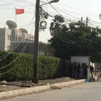 Paramilitary forces and police taCe cover behind a wall during an attack on the Chinese consulate, where blasts and shots are heard, in Karachi, Pakistan Nov. 23. | REUTERS