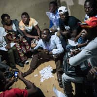 Improvised electoral agents count ballots after a symbolic vote Sunday at Kalinda Stadium in Beni, where voting was postponed for Democratic Republic of Congo's general elections. | AFP-JIJI