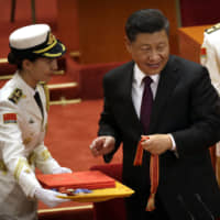 Chinese President Xi Jinping prepares to present a medallion during a conference to commemorate the 40th anniversary of China's reform and opening up policy at the Great Hall of the People in Beijing on Tuesday.   AP