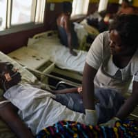Hawanatu Conteh, a nurse at Connaught Hospital, tends to a patient while the hospital's doctors strike over pay and conditions, in Freetown Dec. 4. | REUTERS