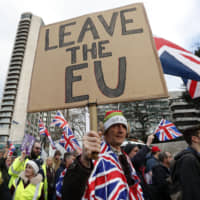 Protesters hold up placards and Union flags as they attend a pro-Brexit demonstration promoted by the United Kingdom Independence Party in central London on Dec. 9. | AFP-JIJI