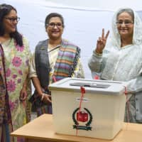 Bangladeshi Prime Minister Sheikh Hasina (right) flashes the victory symbol after casting her vote, as her daughter Saima Wazed Hossain (left) and her sister Sheikh Rehana (center) look on at a polling station in Dhaka on Sunday. | AFP-JIJI