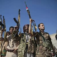 Tribesmen loyal to Houthi rebels hold up their weapons as they attend a gathering to show their support for the ongoing peace talks being held in Sweden, in Sanaa Dec. 13. The United Nations has cast doubt on the claims by Yemen's Shiite rebels to have withdrawn from the port of Hodeida, saying such steps can only be credible if all other parties can verify them. | AP