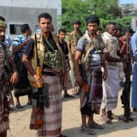 Yemeni Shiite Houthi rebels gather in the port city of Hodeidah Saturday. Yemeni rebels have begun to withdraw from the lifeline port of Hodeida, under an agreement reached in Sweden in December. | AFP-JIJI