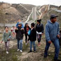 Migrants from Honduras, part of a caravan of thousands from Central America trying to reach the United States, walk next to the border fence as they prepare to cross it illegally, in Tijuana, Mexico, Friday. | REUTERS