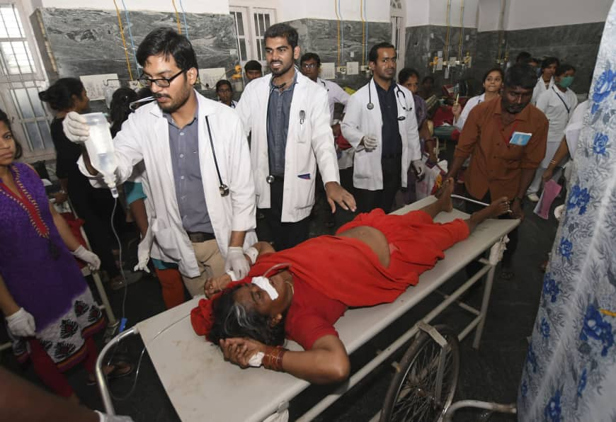 In this Dec. 14 photo, an Indian woman is brought for treatment after a case of suspected food poisoning, at a hospital in Mysore Karnataka state, India. Police on Saturday arrested three people after at least 10 died of suspected food poisoning following a ceremony to celebrate the construction of a new Hindu temple in southern India. | AP