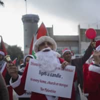 Palestinian protesters, some dressed as Santa Claus, carry Palestinian flags and chant anti Israel slogans during a protest in front of an Israeli checkpoint, in the West Bank city of Bethlehem Sunday. Christians around the world will celebrate Christmas on Monday. | AP