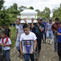 A boy carries a picture of Guatemalan 7-year-old Jakelin Caal, who died in a Texas hospital two days after being taken into custody by U.S. border patrol agents in a remote stretch of the New Mexico desert, as her coffin is taken from Raxruha to the cemetery in San Antonio Secortez, both villages in Alta Verapaz Department, 320 km north of Guatemala City, on Tuesday. Jakelin Caal died after being arrested with her father and others crossing from Mexico into the U.S. on Dec. 6. | AFP-JIJI