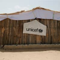 A banner with the UNICEF logo is seen hanging on a makeshift school at an internally displaced persons (IDP) camp on the outskirts of Maiduguri, northeast Nigeria, last year. | REUTERS