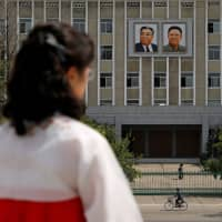 Portraits of late North Korean leaders Kim Il Sung and Kim Jong Il are seen on the facade of a government building in Pyongyang. The top newspaper in the country, which heavily restricts the use of communications devices, wrote Tuesday that 'Erotic notices, fictions and videos, as well as violent electronic games, are spreading through the mobile phones without limits.' | REUTERS