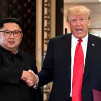 U.S. President Donald Trump and North Korean leader Kim Jong Un shake hands following a signing ceremony during their summit at the Capella Hotel on Singapore's Sentosa Island in June. | AFP-JIJI