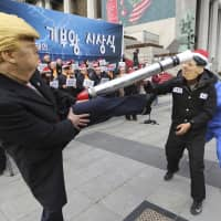 A protester wearing a mask of U.S. President Donald Trump kicks a fellow demonstrator wearing a mask of North Korean leader Kim Jong Un during a rally to denounce policies of South Korean President Moon Jae-in toward the North in Seoul on Tuesday. | AP