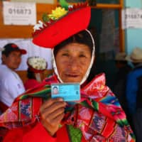 A woman shows her identity card at a polling station in Ollantaytambo, a town in what is known as the Sacred Valley of the Incas, in Urubamba province in the Cusco region of Peru, as the country voted Sunday on President Martin Vizcarra's constitutional reforms aimed at eradicating corruption. | AFP-JIJI