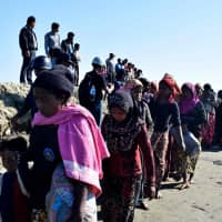 Myanmar Navy personnel escort Rohingya Muslims back to their camp in Sittwe, Rakhine state, on Friday. Nearly 100 Rohingya Muslims were forced back to Rakhine state after being detained at sea en route to Malaysia, police said on Nov. 28, stirring fears of a fresh refugee boat crisis. | AFP-JIJI