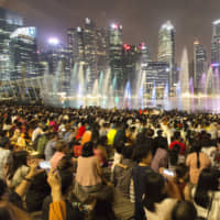 People take photographs as they watch the Spectra light and water show at the Marina Bay waterfront in Singapore in February. | BLOOMBERG