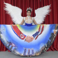 Singaporean model Zahra Khanum, Singapore's representative to the upcoming Miss Universe pageant, shows off a dress on Nov. 28 depicting a key moment of the U.S.-North Korea summit that Singapore hosted earlier this year. | STRAITS TIMES / VIA KYODO