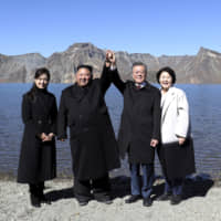 South Korean President Moon Jae-in (second from right) and his wife, Kim Jung-sook (right), stand with North Korean leader Kim Jong Un and his wife, Ri Sol Ju, on Mount Paektu in North Korea on Sept. 20.   POOL / VIA AP