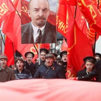 Demonstrators carry flags and a portrait of Soviet state founder Vladimir Lenin during a rally held by the Russian Communist party to mark the Red October revolution's centenary in central Moscow last year. | REUTERS