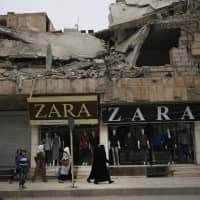 Women walk in front of clothing shops on a street in Manbij, north Syria, in March. On Friday, Syria's military announced it had taken control the flash-point Kurdish-held town. | AP