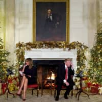 U.S. President Donald Trump and first lady Melania Trump participate in NORAD Santa tracker phone calls from the White House in Washington Monday. | REUTERS