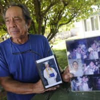 Clifford Kang, father of soldier Ikaika E. Kang, poses with photos of his son in Kailua, Hawaii, last year. Ikaika E. Kang, an active-duty U.S. soldier, arrested on terrorism charges that accuse him of pledging allegiance to the Islamic State group, is scheduled to be sentenced Tuesday. | BRUCE ASATO / HONOLULU STAR-ADVERTISER / VIA AP