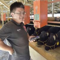 Yoshitaka Nakao of Nakao livestock farm in Mie Prefecture, holds a smartphone at his farm on Sept. 28, 2018. | KYODO