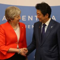 British Prime Minister Theresa May and Prime Minister Shinzo Abe shake hands during a bilateral meeting in Buenos Aires on Saturday. | REUTERS