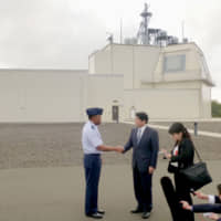 Then-Defense Minister Itsunori Onodera (second from left) visits a test complex for the Aegis Ashore missile defense system on the Hawaiian island of Kauai on Jan. 10. | KYODO