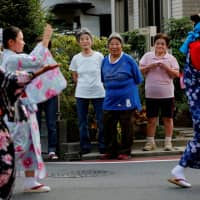 Residents watch folk dancers parade during a festival in the Sennari district of Sakura, Chiba Prefecture, in July. | REUTERS