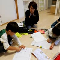 Motoko Hagiwara watches as her children do their homework in the living room of their house in the Higashinohara district in Inzai, Chiba Prefecture, on Nov. 6. | REUTERS