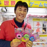 Naoya Igarashi, manager of Game Center Everyday in Gyoda, Saitama Prefecture, holds prizes for a claw machine last week. The machine features goods that bring back memories of earlier days in the Heisei Era. | KYODO
