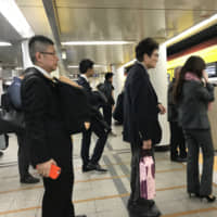 A man waits for a train in Tokyo in November while carrying his backpack on his front. | SARAH SUK