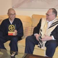 The Rev. Kenjitsu Nakagaki, a Buddhist monk based in New York City, holds a copy of his book, 'The Buddhist Swastika and Hitler's Cross,' while speaking with Rabbi Alan Brill, chair of Jewish Christian studies at Seton Hall University in New Jersey, at the university in November. | KYODO