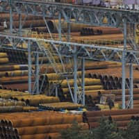 Levy metal: Steel pipes sit stacked near the Nippon Steel & Sumitomo Metal Corp. plant in Kashima, Ibaraki Prefecture. | BLOOMBERG