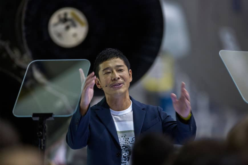 Yusaku Maezawa speaks near a Falcon 9 rocket during an announcement named him as the first private passenger who will fly around the moon aboard the SpaceX BFR launch vehicle.