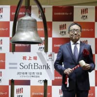 Ken Miyauchi, president and CEO of Softbank Corp., prepares to strike the trading bell at the Tokyo Stock Exchange ahead of the company's debut there on Dec. 19. | KYODO