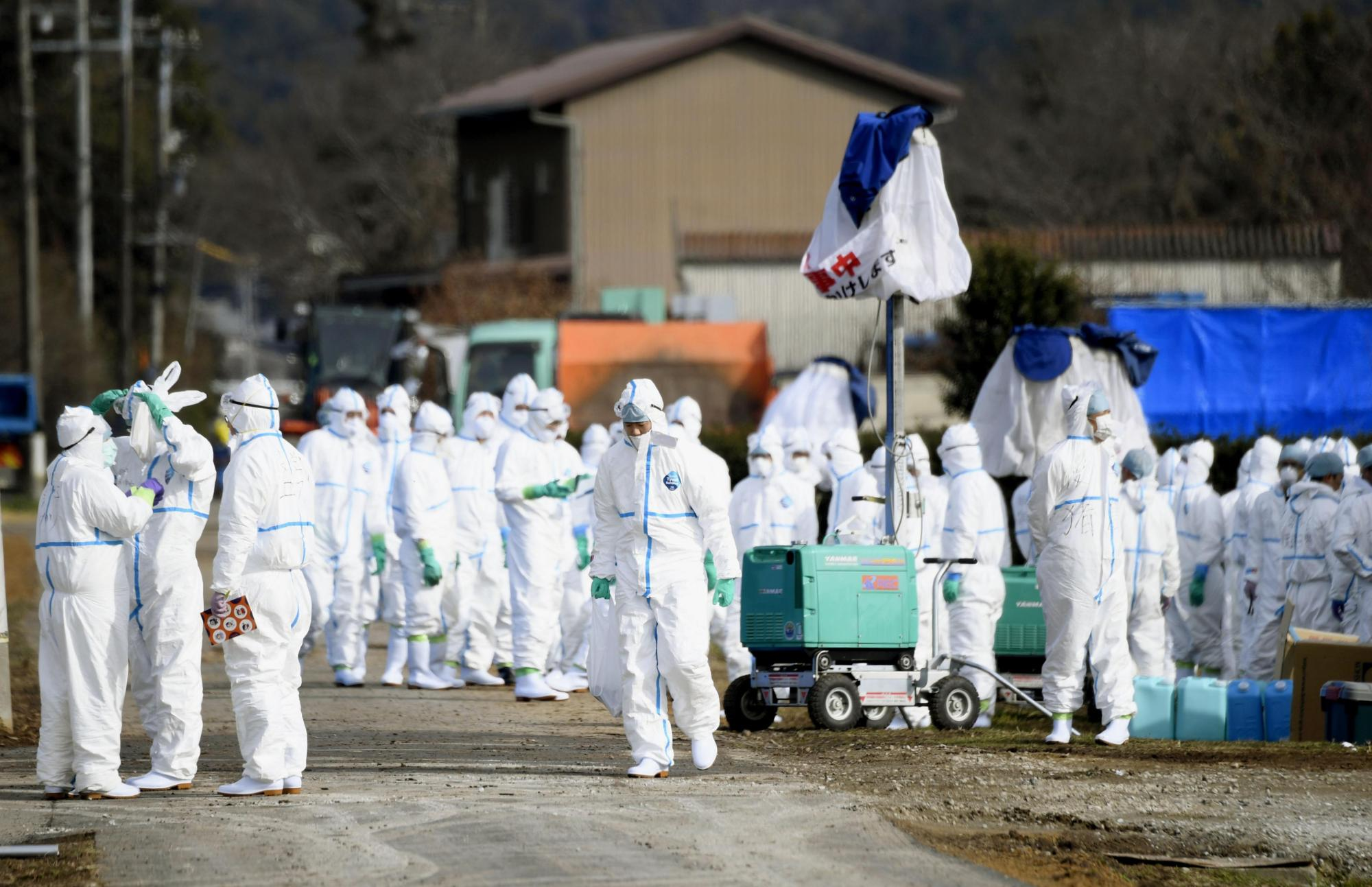People in protective gear gather near a pen on Tuesday in Seki, Gifu Prefecture, following the detection of swine fever in one of the pigs kept there. | KYODO