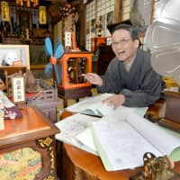 Junno Nakamura, chief priest of Saihoji Temple in Kota, Aichi Prefecture, sits in a room with an antique record player and Edo-style mechanical dolls that he made. | CHUNICHI SHIMBUN