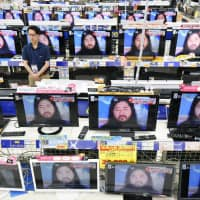 Television screens at an electronics store in Tokyo broadcast the news of Aum Shinrikyo founder Shoko Asahara's execution. | KYODO