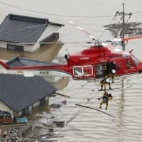 A rescue team extracts a person from a badly flooded area of Kurashiki, Okayama Prefecture, on July 7 following torrential rains. | KYODO