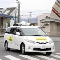 An autonomous car trial is conducted in the town of Namie, Fukushima Prefecture, on Dec. 3. | KYODO