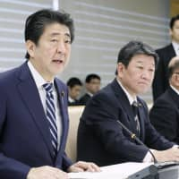 Prime Minister Shinzo Abe speaks at a ministerial meeting held Friday to approve a program to expand child care and higher education support. | KYODO