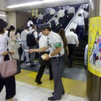 A JR East official asks commuters to use escalator handrails at Tokyo Station in July. This month Tokyo Station is launching a similar campaign to discourage walking on escalators.  | KYODO