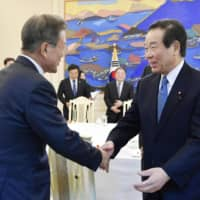 South Korean President Moon Jae-in greets Fukushiro Nukaga, a Liberal Democratic Party lawmaker who leads a parliamentary group tasked with improving ties with South Korea, during a meeting Friday in Seoul. | KYODO