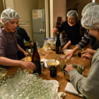 Ami Takahashi (left) instructs participants Friday at her weekly jam and ponzu sauce-making session held at Yuzuriha in Kokubunji, Tokyo. A portion of product sales are given to the workshop participants as wages. | YOSHIAKI MIURA