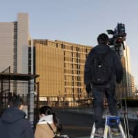 TV crews stand in front of the Tokyo Detention Center, where former Nissan Chairman Carlos Ghosn and another former executive, Greg Kelly, are being detained, in Tokyo on Friday. | AP