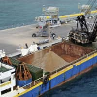 Soil and sand is loaded onto a vessel Monday at a pier in Nago, Okinawa Prefecture, to prepare for reclamation work for a replacement site for U.S. Marine Corps Air Station Futenma off the coast of Henoko. | KYODO